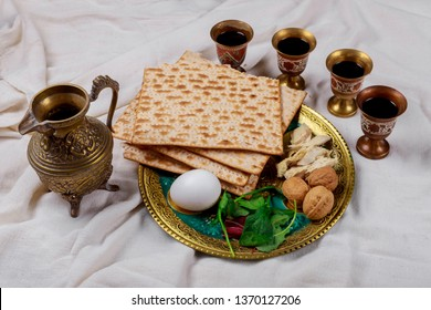 Passover matzoh jewish holiday bread, four glasses kosher wine over table.