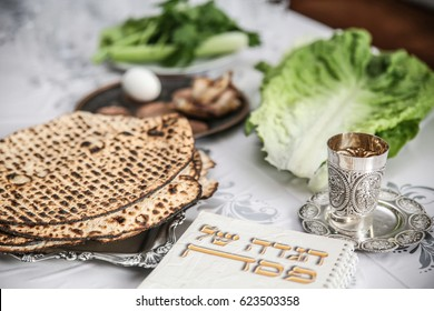 Passover Seder Plate with The seventh symbolic item used during the seder meal on passover Jewish holiday.  (Kiddush cup, haggada, matzos, lettuce, an arm)