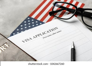 Passport, American flag and visa application form on table. Immigration to USA