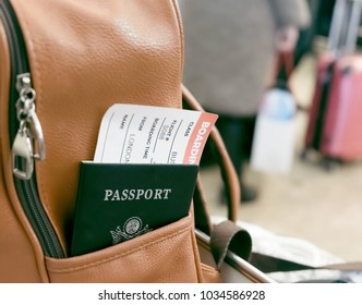 Passport with boarding pass in the pocket of a leather backpack at the airport