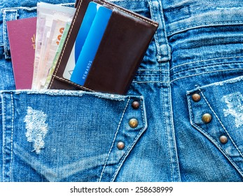 Passport book and wallet in back blue jeans pocket/ traveling concept