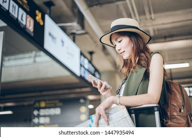 Passport checking online on phone - Travelers Asian woman flight schedules on a mobile phone in the airport preparing to board the plane