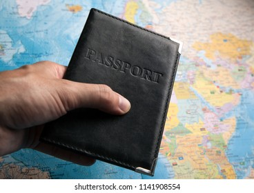 passport of a citizen in the hand of a person on the background of a map of the world