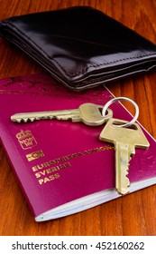 Passport with keys to a home and wallet on wooden tabletop. The top three things to bring and keep safe on your journey.