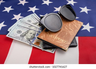Passport, money, and glasses, on the American flag