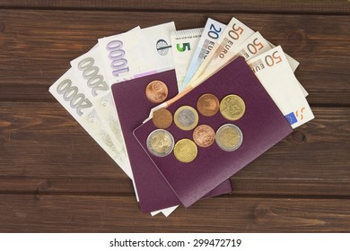 Passport and money on wooden table. Valid EURO banknotes, coins and banknotes Czech. Illegal migration for money. Paying smugglers for crossing the border.