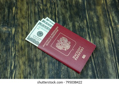 The passport of Russia with dollars lies on a wooden table.