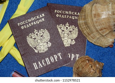 Passport Russian on a blue background, swimsuit, hat, glasses, perfume, shells.