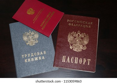 Passport and seniority, working book, pension certificate on a dark background.