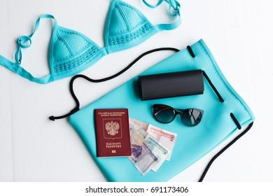 passport, sunglasses, case, money, backpack, bikini lying on white background
