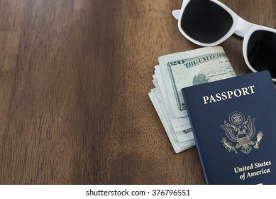 passport, sunglasses and dollar bills isolated on wooden table as travel concept. Has copy space.