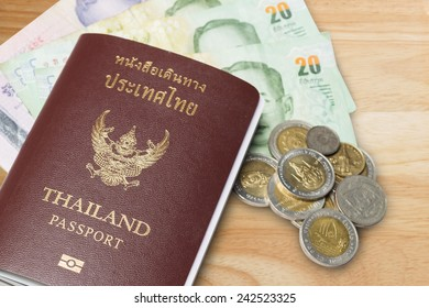 Passport of thai and money on wood background.