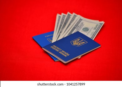 Passport of ukraine with money dollars inside on a red background. Concept of travel, selective focus.