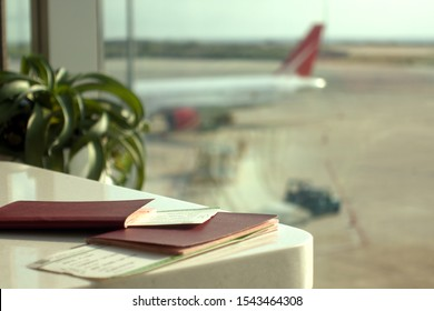 Passports and boarding passes on a table in an airport lounge against the blurred airplane and tarmac window view.