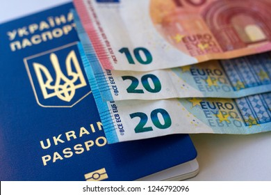Passports of citizens of Ukraine for traveling abroad and three Euro notes. Concept on the theme of travel on low-cost aircraft. Cheap flights Ukrainians in Europe.