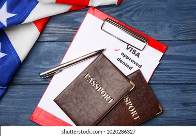 Passports with clipboard and USA flag on wooden background. Approved American visa