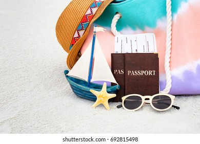 Passports and tickets with beach accessories on sand. Summer vacation concept