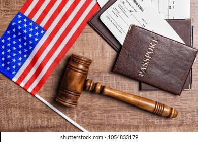 Passports, tickets, gavel and American flag on table. Legal immigration
