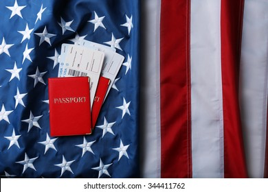 Passports, tickets lying on American Flag background