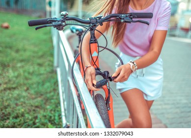 Password selection for protection. Girl locks bike parking lot. Concept of protecting property thieves, selection cipher code. lock with cipher metal cable theft bicycle. Summer city bicycle walk.
