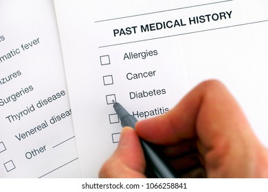 Past medical history questionary. Person hand with pen ready to ticked Diabetes. Close-up.