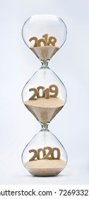 Past, present and future concept. 3 part hourglass. Falling sand taking the shape of years 2018, 2019 and 2020.