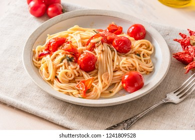 Pasta al pomodoro - spaghetti with cherry tomatoes on a plate close-up in a rustic style