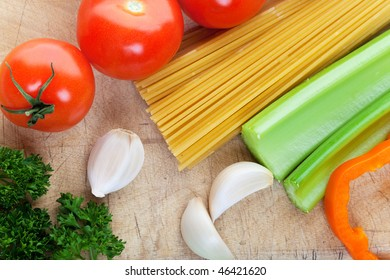 Pasta along with fresh vegetables on a wooden cutting board
