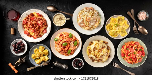 Pasta. Assortment of Italian pasta dishes, including spaghetti Bolognese, penne with chicken, tortellini, ravioli and others, shot from the top on a black background