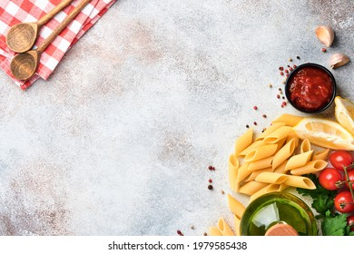 Pasta background. Pasta rigati, tomato ketchup sauce, olive oil, spices, parsley, and fresh tomatoes on a light grey slate table. Food cooking background. Top view with copy space.
