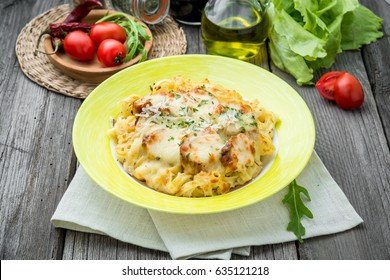Pasta bake with broccoli and chicken. On a wooden table