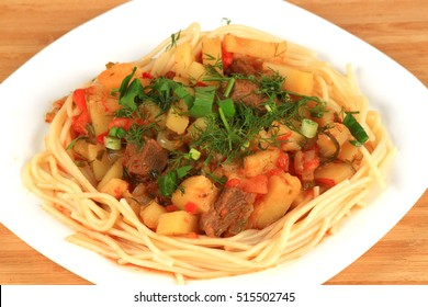 Pasta and beef goulash on a white plate