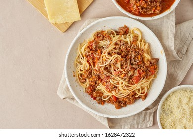 Pasta Bolognese with spaghetti, mincemeat and tomatoes, parmesan cheese. Italian cuisine, terracotta background. Homemade fresh food. Top view, copy space
