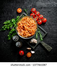 Pasta in a bowl with tomatoes,herbs and garlic. On rustic background