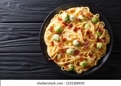 Pasta with Brussels sprouts, ham covered with creamy cheese sauce close-up on a plate on the table. horizontal top view from above