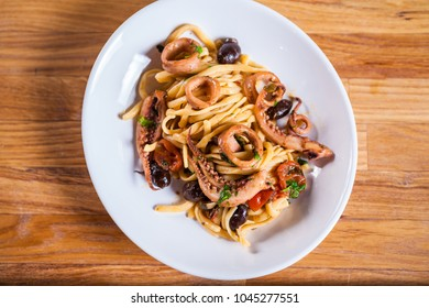 Pasta with calamari seasoned with red cherry olives and basil. Calamari spaghetti on white plate. Mediterranean pasta. seafood. Italian food. Fine dish. Fres food