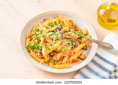 Pasta caponata on a plate on a light rustic table