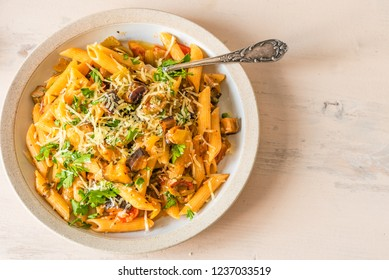 Pasta caponata on a plate on a light rustic table. Recipe copy space