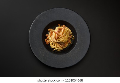 pasta carbonara with bacon in a black plate isolated on a black background.