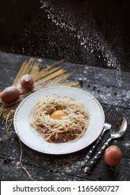 Pasta carbonara on a dark wooden background, raw ingredients on the table - eggs and spaghetti, the dish is sprinkled with flour