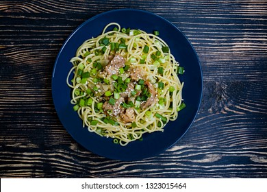 Pasta carbonara with pork, fresh herbs, sprinkled with sesame on top of a blue plate. Dark wooden background. View from above.