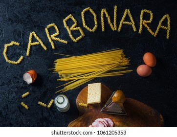"""Pasta Carbonara. Spaghetti with bacon and parmesan cheese. Pasta Carbonara on white plate with parmesan on dark background with word """"Carbonara"""". Italian food concept. Top view"""