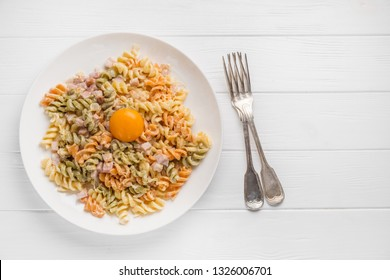 Pasta carbonara in white plate on white wooden background. Flat lay.