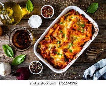 Pasta casserole with minced meat, mozzarella cheese and vegetables on wooden table