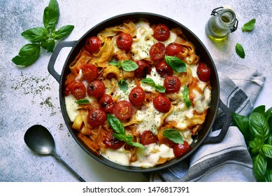 Pasta casserole with tomatoes and mozzarella cheese in a black iron pan on a light grey slate, stone or concrete background. Top view with copy space.