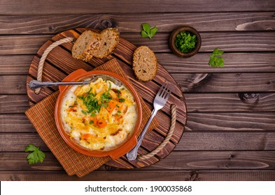Pasta casserole with vegetables in a ceramic dish on a wooden background. Selective focus.