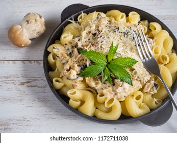 Pasta cavatappi with cepes in a iron pan on the wood table.