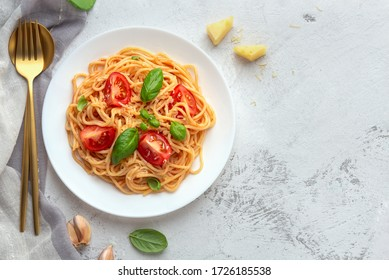 Pasta with cherry tomatoes, cheese and basil on a light background. High key, top view, copy space