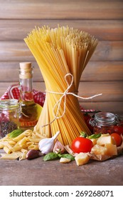 Pasta with cherry tomatoes and other ingredients on wooden background