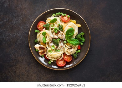 Pasta Chicken Primavera. Spaghetti pasta with grilled chicken meat, vegetables and basil, top view, copy space. Seasonal pasta primavera recipe.